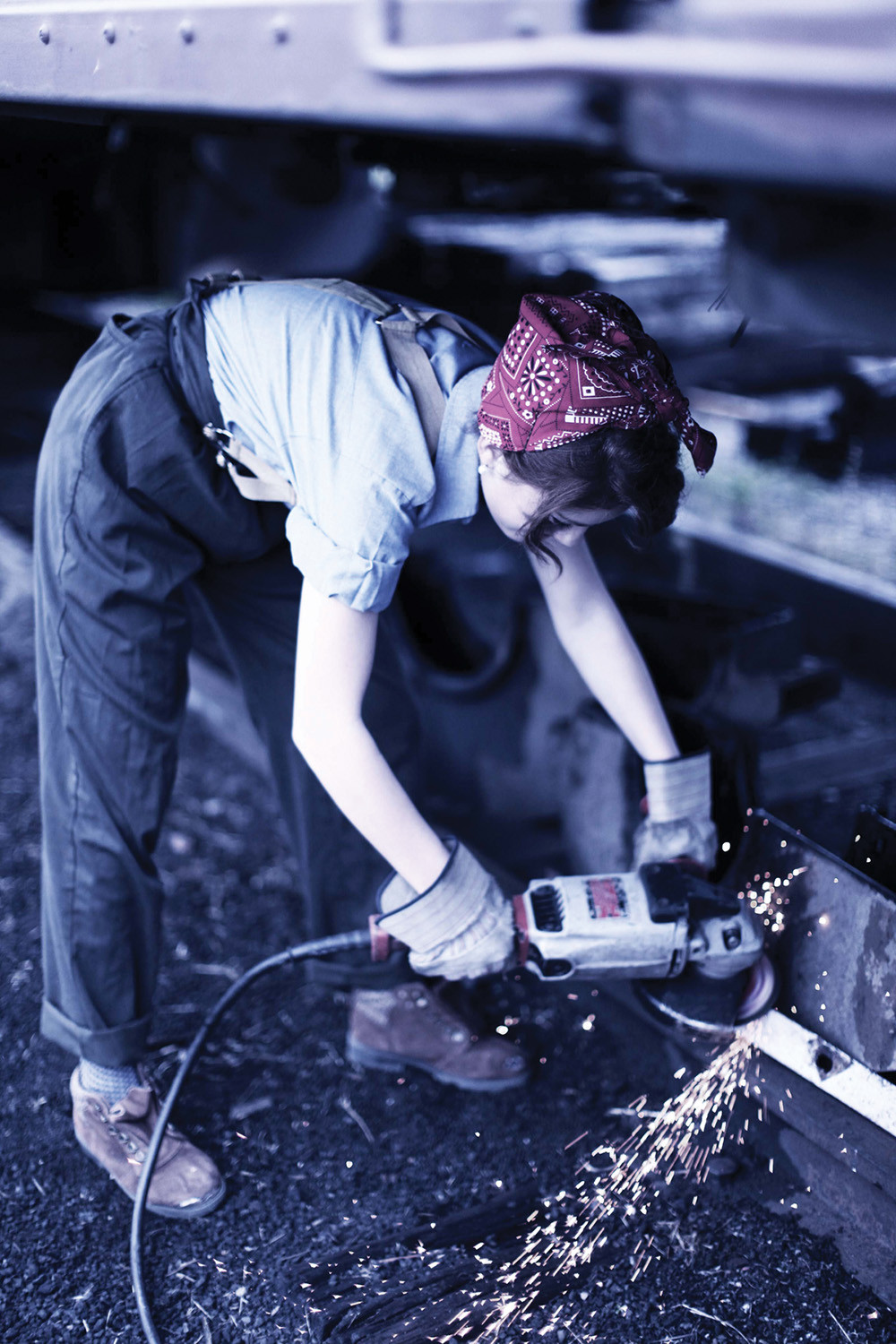 young woman in 1940's mens work clothes do rag and gloves grinds down metal on the train with grinder