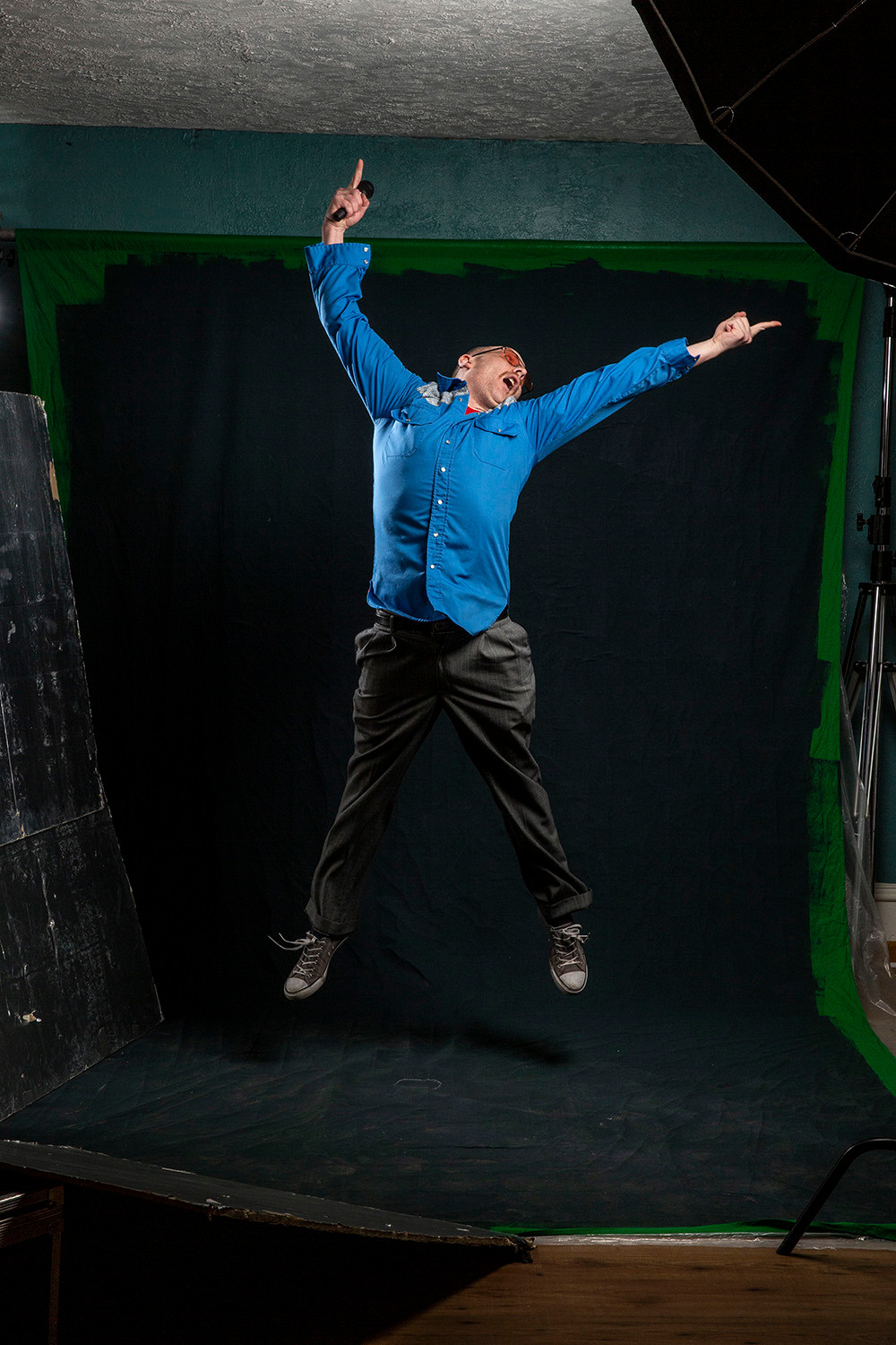comedian Nate Barron jumps high in the air with a microphone in hand and all limbs outstretched in all directions