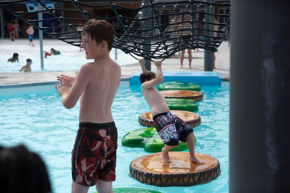 A young boy waits his turn while his brother challenges himself to cross the lap pool at River Rapids on floating foot pads and a hanging net