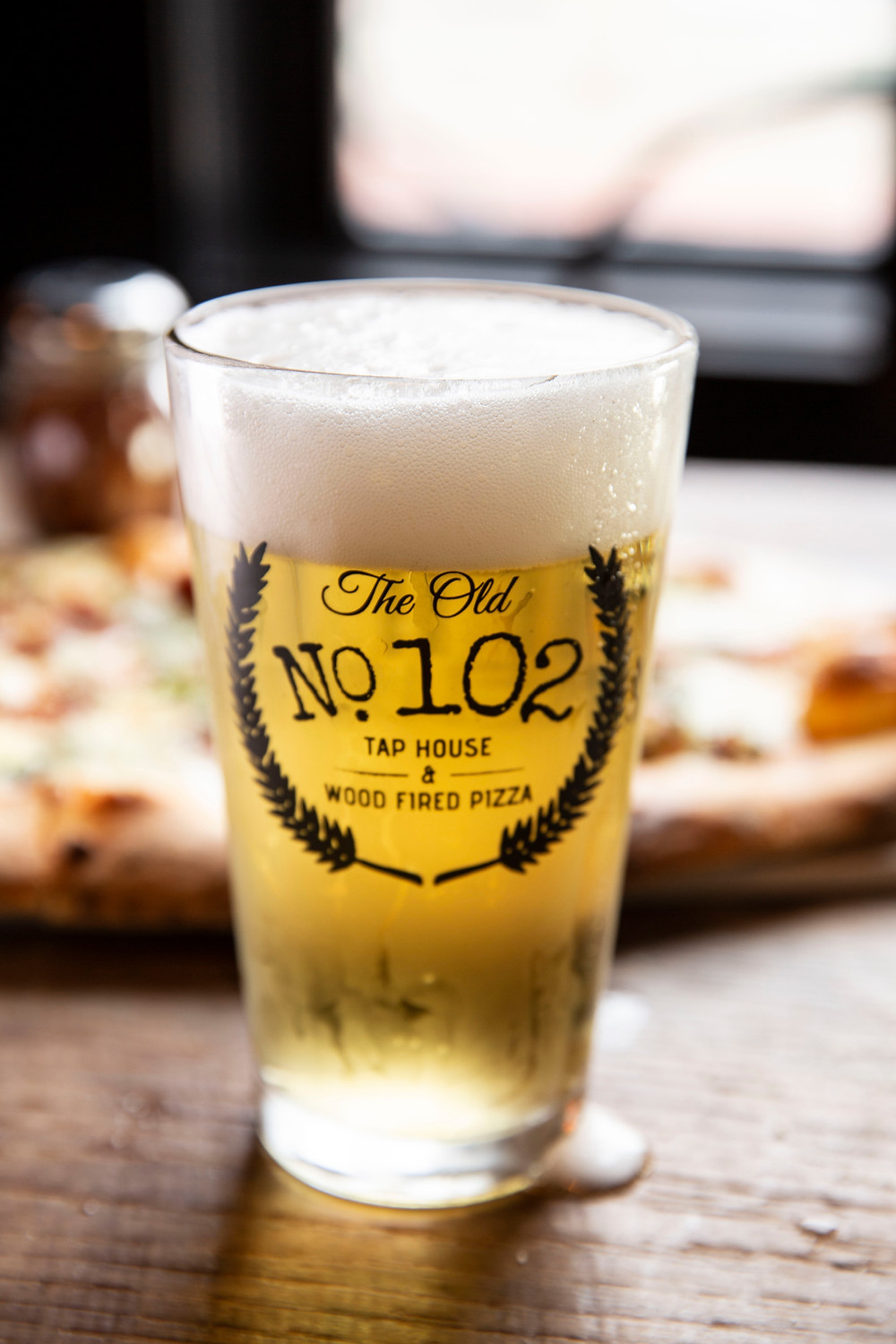 """Large glass of beer with a foamy top with """"The Old No. 102 Tap House & wood fired pizza"""" printed on it stands in front of a large pizza"""