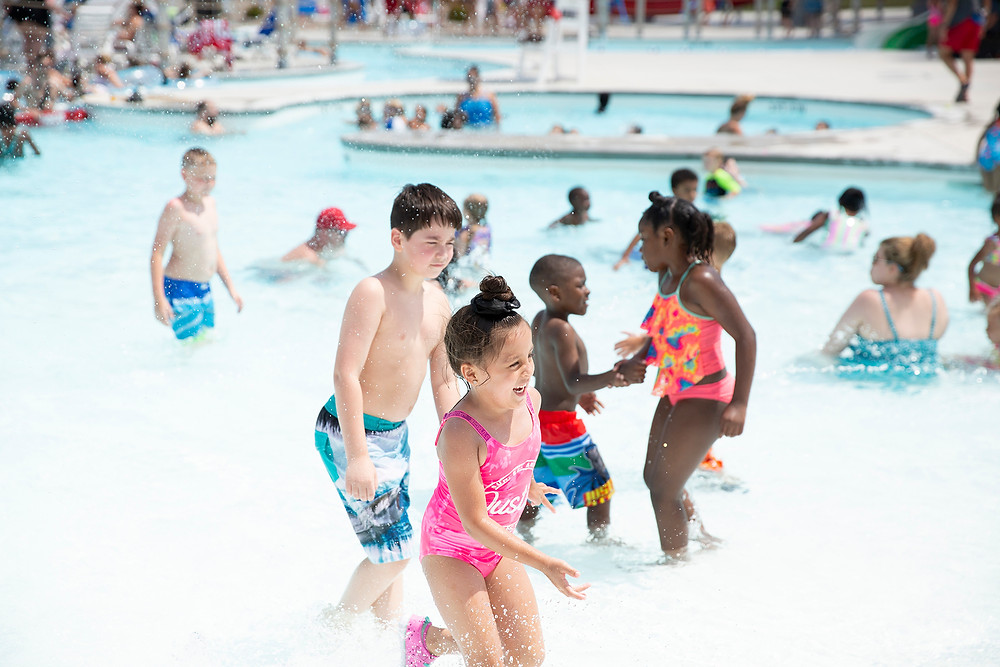 A large variety of different families splash and play in the water at River Rapids Water Park
