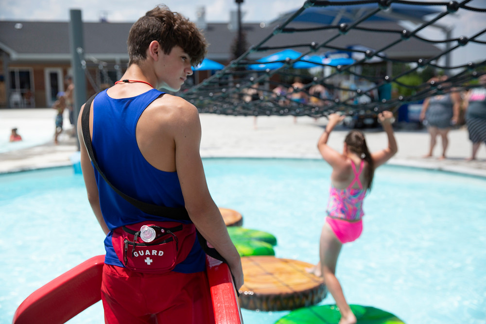 A young man with a red lap float and lifeguard fanny pack watches the pool as a young girl crosses on the floating foot pads