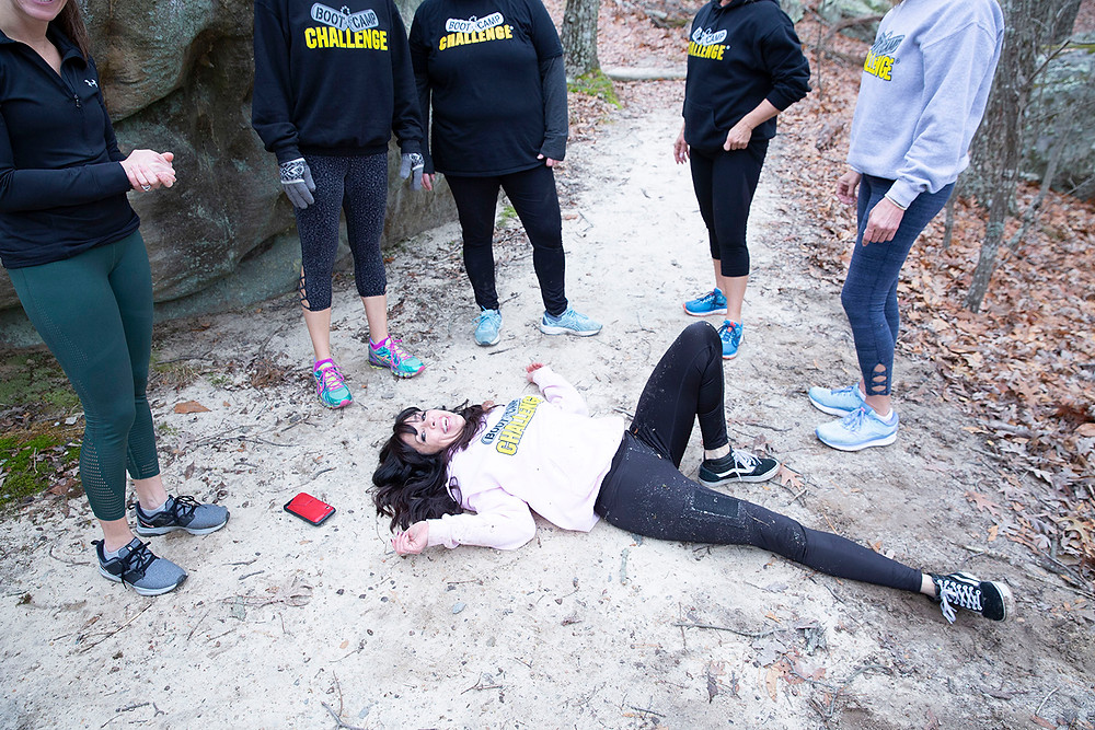 Personal trainer, Tamatha Crowson sprawls out on the ground as her class stands around her in the forest