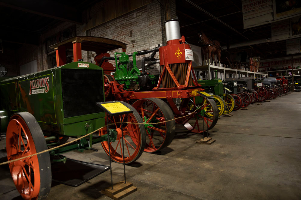 A long row of beautiful antique tractors roped off and lined up in the American Tractor Museum