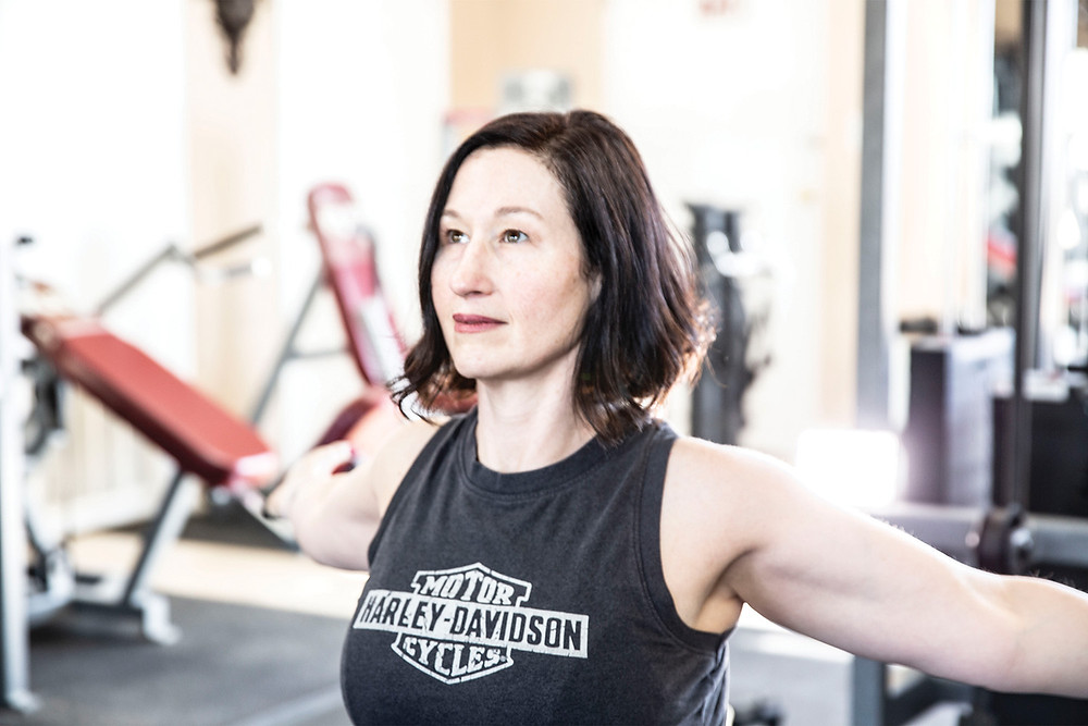 Attractive woman in a Harley-Davidson tank top stretches her arms back while using the machinery in a gym