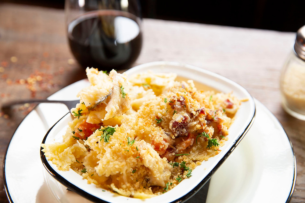 a fork scoops a bite of butterfly pasta alfredo with bits of bacon, chicken, and herbs next to a glass of red wine