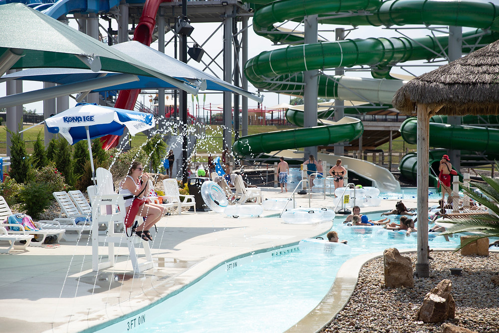A life guard under the shade of an umbrella watches park goers float down the lazy river at River Rapids with the giant water slides towering behind