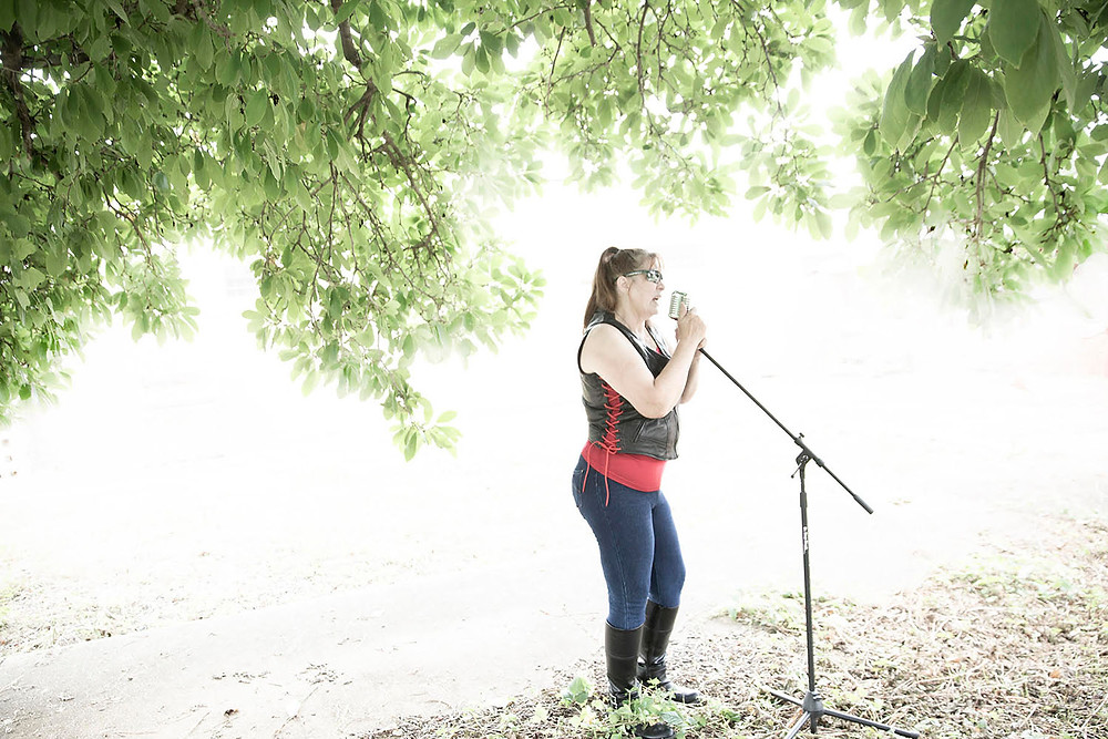 Brunette woman with sunglasses and black leather biker vest sings into classic chrome microphone under a large tree