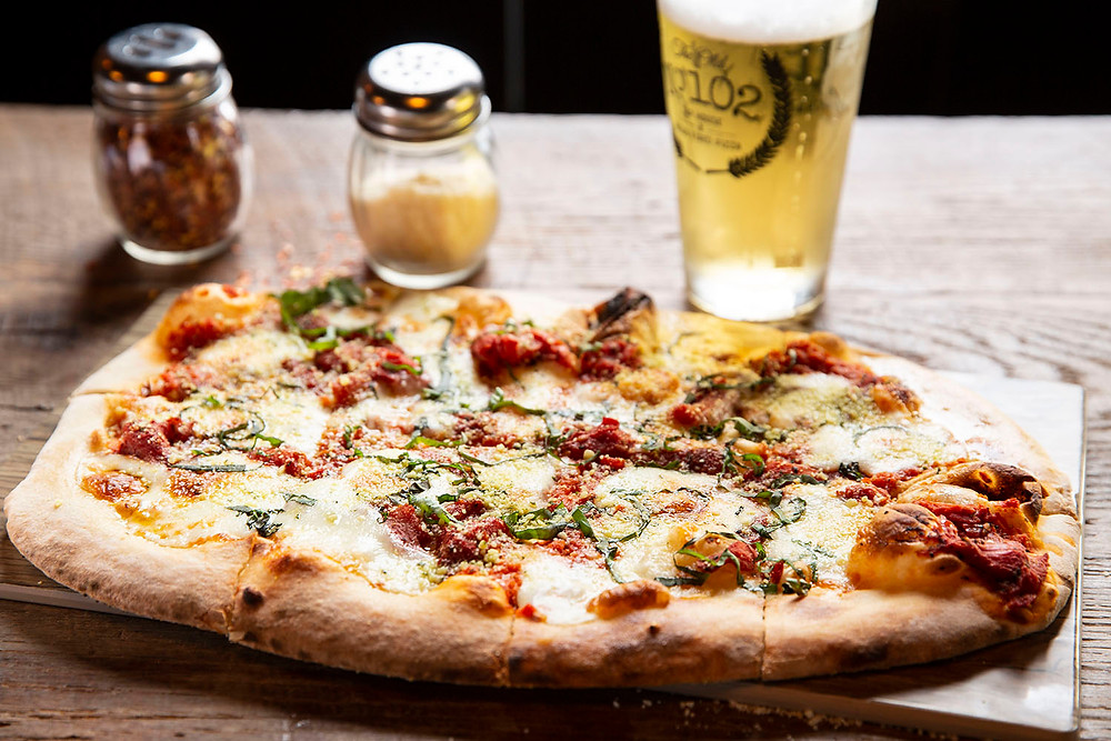 Large brick oven pizza by a tall glass of beer, a parmesan shaker, and a red pepper shaker