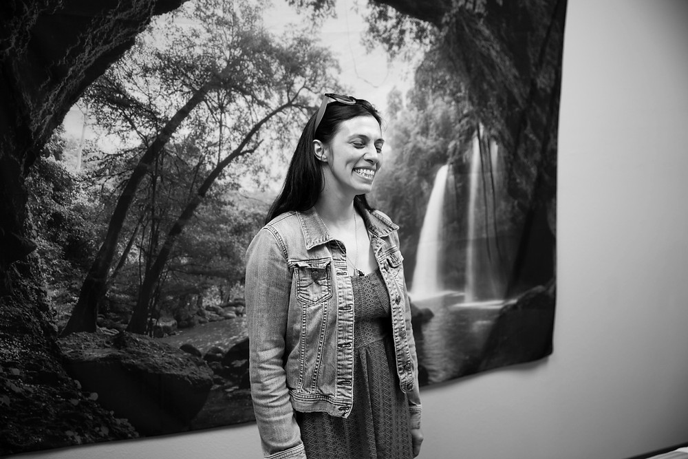 Woman smiles in front of scenic picture of forest and waterfall