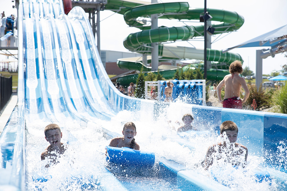 4 children fly down a four lane mat racing water slide with water splashing up all around at River Rapids