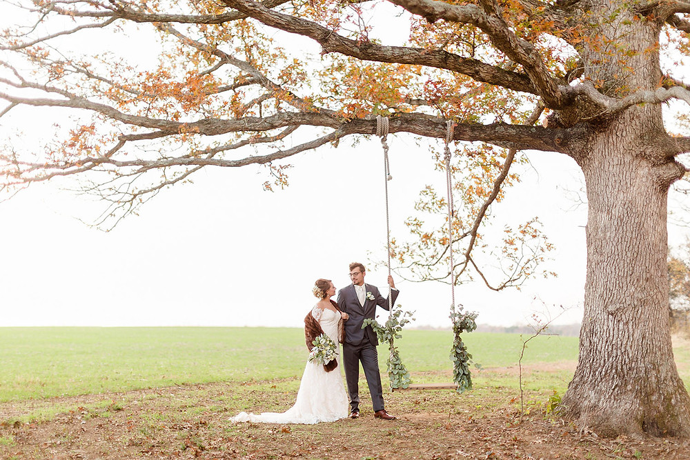 wooden swing in a big oak tree photo op with bride and groom at The Barn at Lone Eagle Landing wedding venue