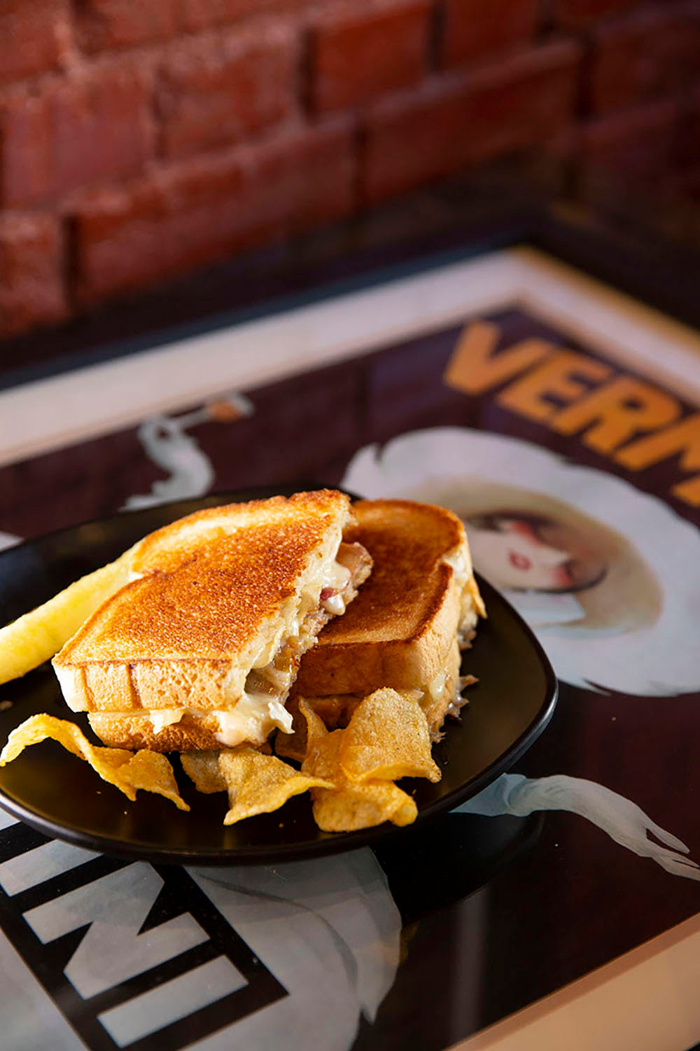 Golden grilled cheese with bacon sandwich cut in half on a plate with bar-b-que chips