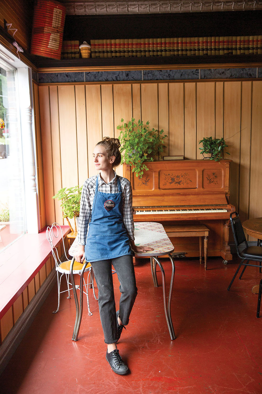 young blonde woman with bun in apron leans against table with player piano in background and stares out large front window