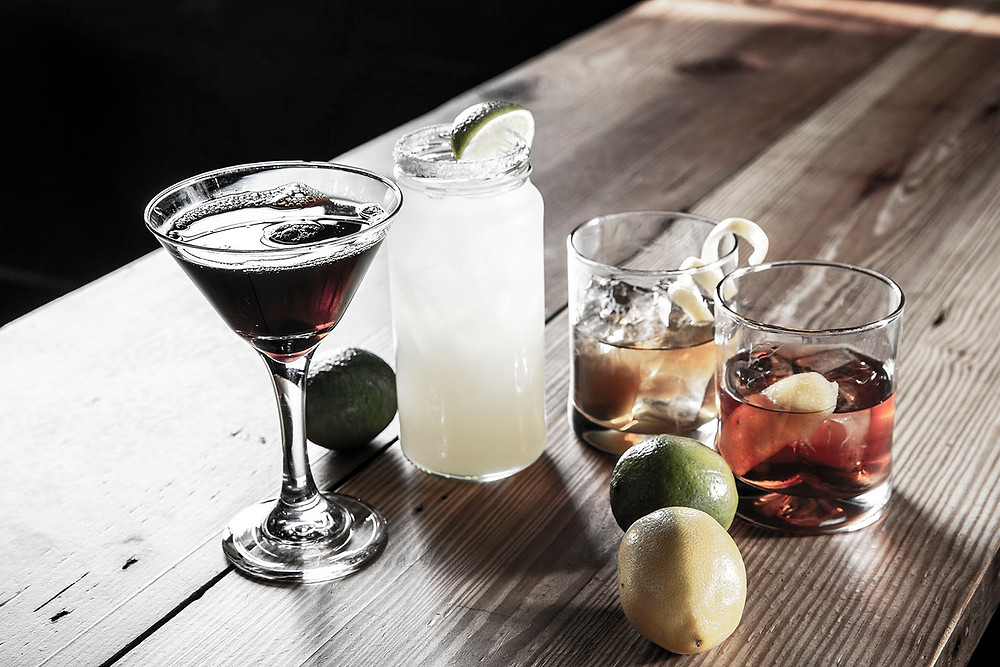 Four beautiful mixed drinks in glasses of varying shapes and sizes garnished with fresh fruit by whole lemons and limes