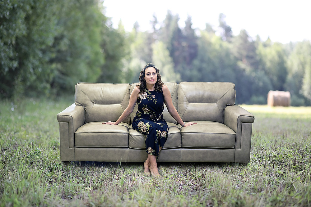 young woman sits on a leather couch in an open field with a treeline in the distance