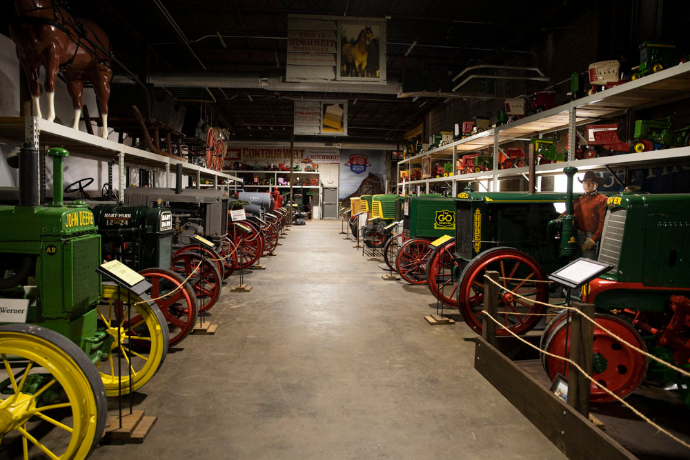 A long hall in the American Tractor Museum with rows of antique tractors lined up on either side