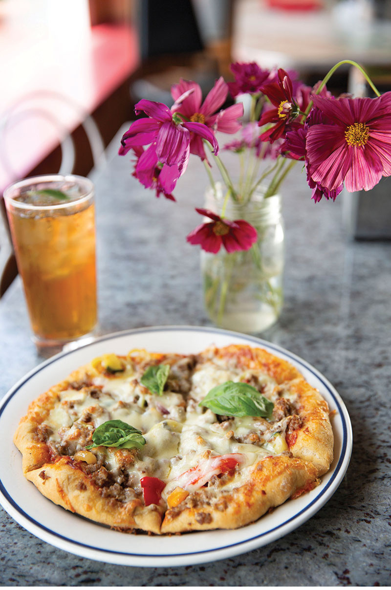 hand tossed personal pizza with basil leaf garnish and herbal bliss tea with mint leaf garnish by bright pink wild flowers
