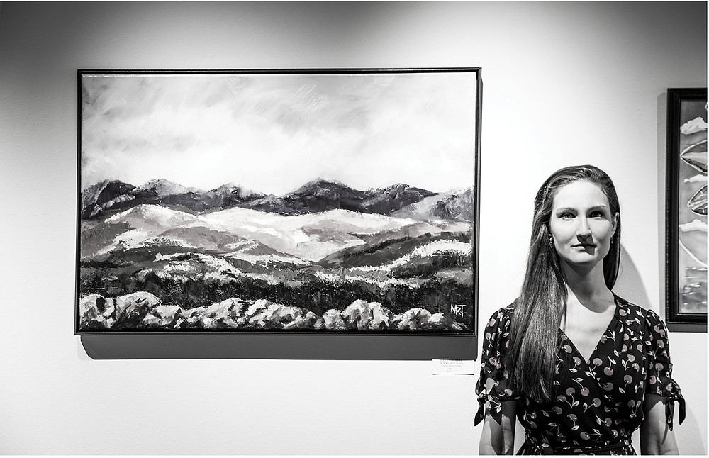Young attractive woman stands to the side of a painting of mountains and a rocky foreground at the Arts Council