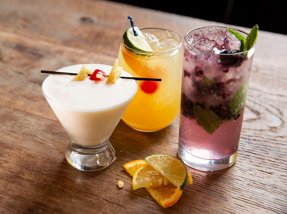 3 beautiful cocktails of different shapes sizes and color garnished with fresh fruit at The Old No. 102 Tap House