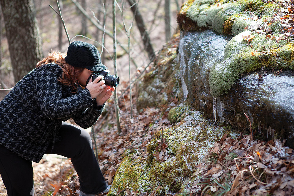 young woman leans in close with her camera to get a shot of the crystal looking reindeer moss encased in ice