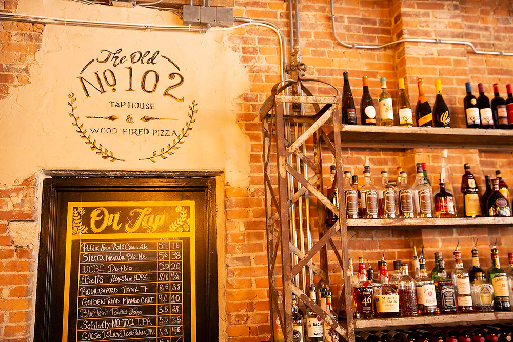 Brick wall with liquor shelf and On Tap sign listing craft beers at The Old No. 102 Tap House
