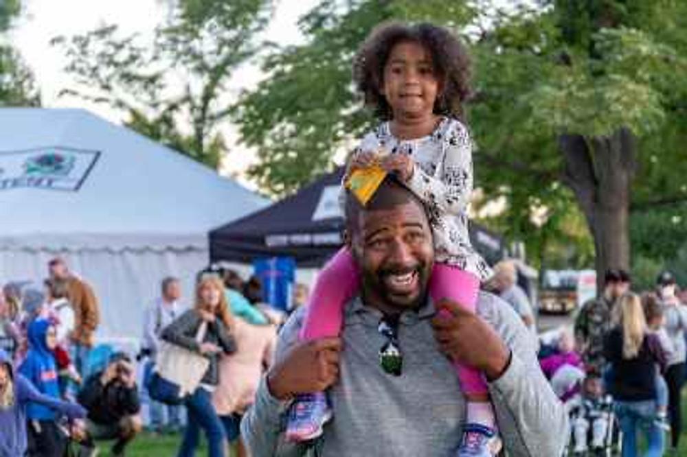 girl sitting on smiling man s shoulder