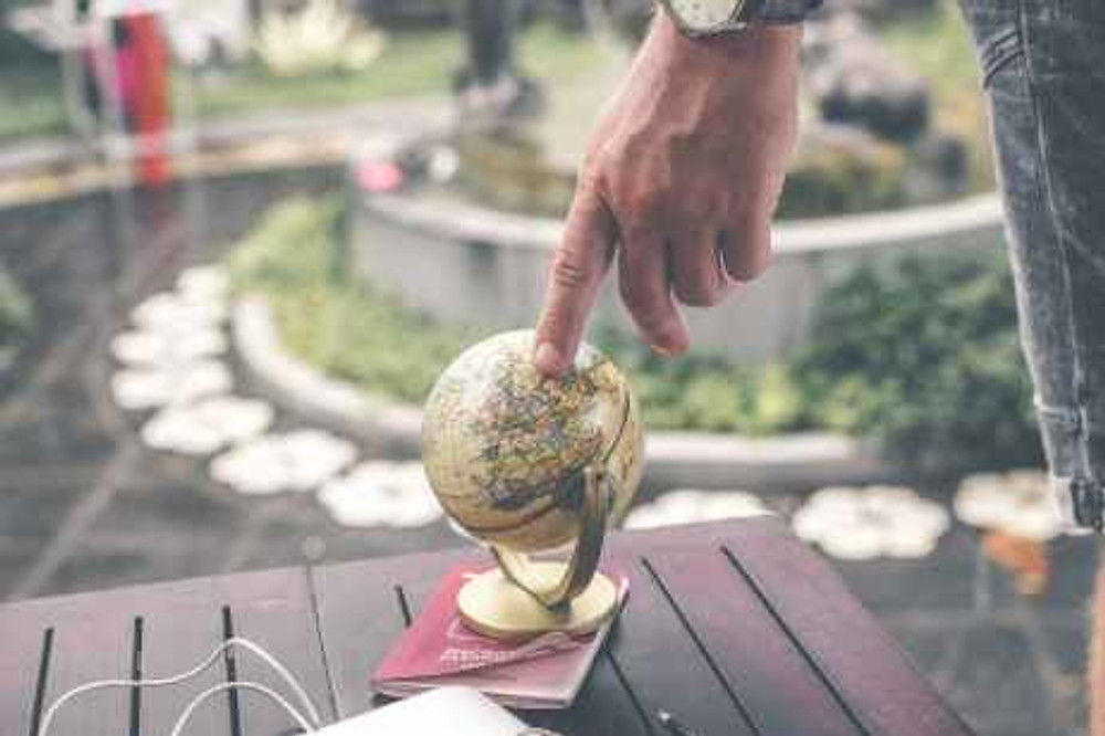 person holding terrestrial globe scale model taken