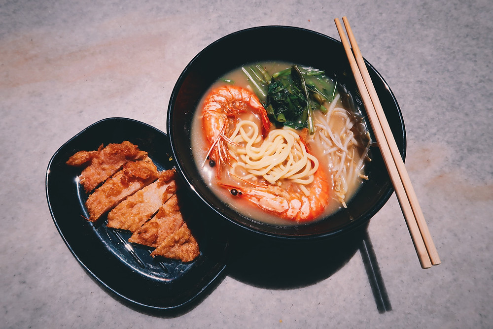 Bowl of prawn noodles with prawn paste pork chop by the side