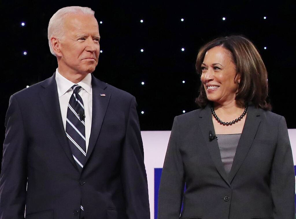 Kamala Harris looks at Biden, Biden looks out at the crowd.
