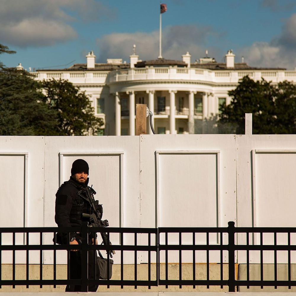 """Soldier with gun outside the White House infront of an """"unscalable"""" wall."""