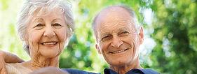 An elder white man with his arm around an elder white woman, smiling.