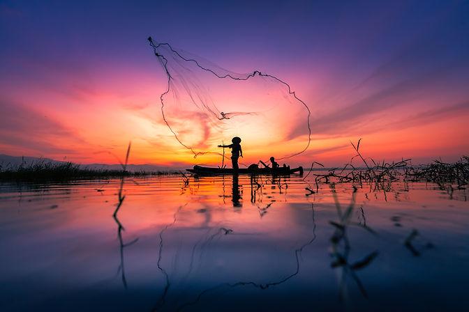 Silhouette of Myanmar fisherman on woode