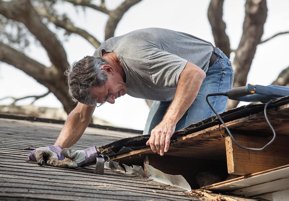Man on roof fixing damage