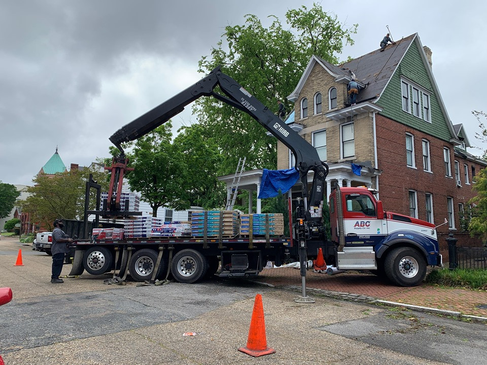 A flatbed truck with roofing materials preparing to begin a roof installation project.