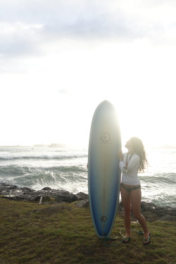 girl and her surfboard with waves in the background,Kahului Harbor, Maui, USA