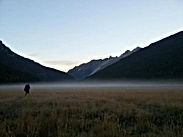 A hiker crossing a misty meadow in the mountains