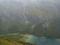 Looking down into a valley with a turquoise lake and waterfalls far in the backround.