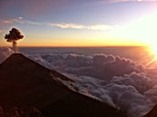 The silhouette of an erupting volcano on the left with a setting sun on right over a sea of clouds