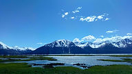 Snowcapped mountains behind a waterway with green grass and blue sky