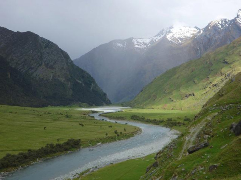 A river winding through a mountainous valley with snow on peaks