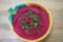 bowl of vibrant purple beet dip garnish with herbs