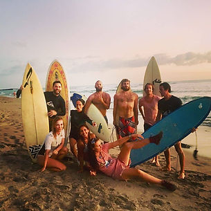 group of friends with surfboards on sandy beach