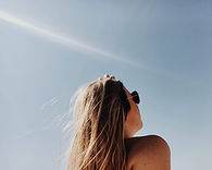 a blonde girl with sunglasses looking up at a sunny sky