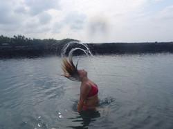 a woman whipping her wet hair back, in the ocean near Beach 69, Big Island, Hawaii, USA