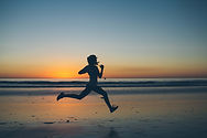 A runner sprinting on a beach at sunset