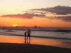 father and sun watching a fiery sunset inTamarindo, Costa Rica