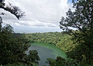 Birds eye view of a green crater lake framed by trees