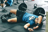 A tired man lays on the floor in the gym