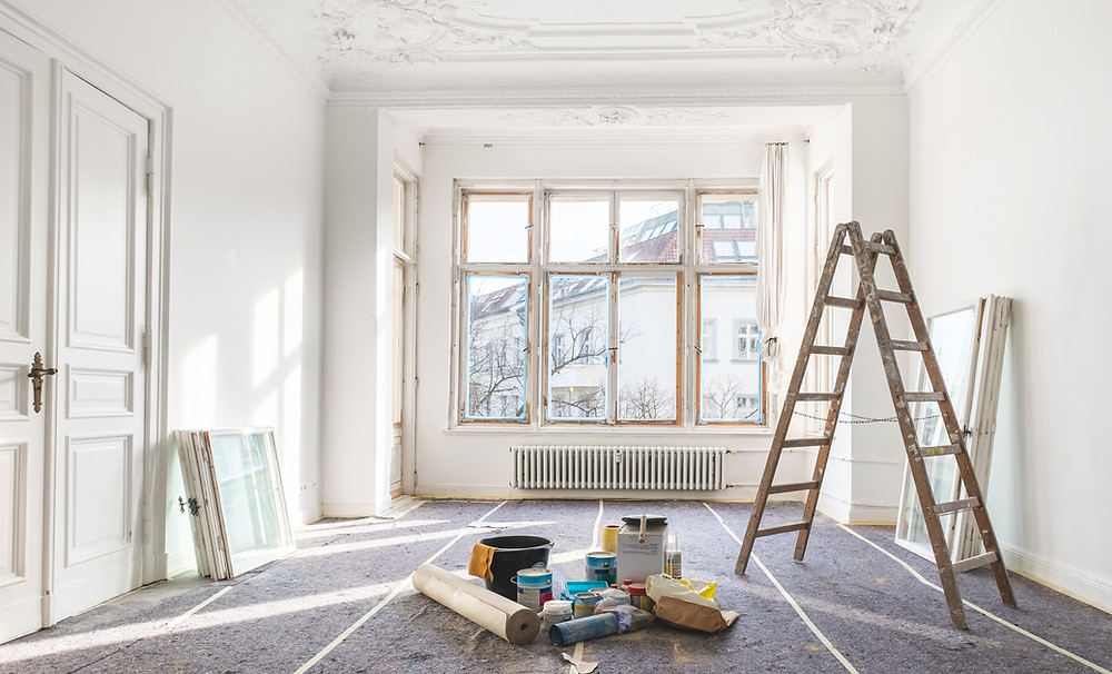 white room with large windows and a ladder paint cans on floor